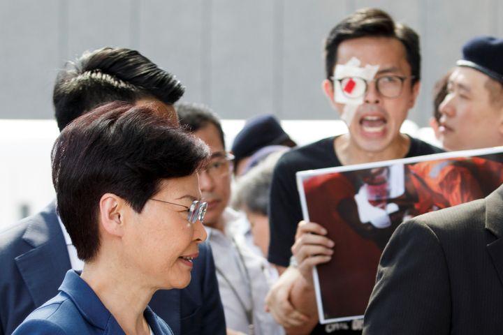 La cheffe du pouvoir exécutif de Hong Kong, Carrie Lam, passe devant des manifestants, devant son bureau, à Hong Kong, le 13 août 2019. (THOMAS PETER / REUTERS)