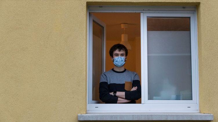 Jonathan Peterschmitt, un médecin infecté par le coronavirus, pose à la fenêtre de son cabinet médical, àBernwiller (Haut-Rhin), le 4 mars 2020. (SEBASTIEN BOZON / AFP)