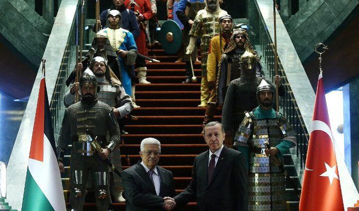 Erdogan et Abbas sur un escalier du palais présidentiel turc entouré de gardes en costumes d'époque. (ADEM ALTAN / AFP)