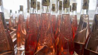 Des bouteilles de vin rosé sur une ligne d'embouteillage. (CHRISTIAN WATIER / MAXPPP)