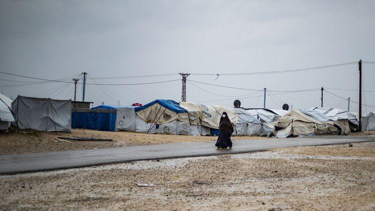 Une femme passe devant des tentes sous la pluie au Camp Roj (Syrie), où sont détenus des proches de personnes soupçonnées d'appartenir au groupe État islamique, le 4 mars 2021. (DELIL SOULEIMAN / AFP)