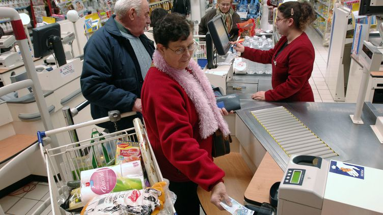 Une cliente paie en liquide à une caisse d'un supermarché, en décembre 2007. (FRANK PERRY / AFP)