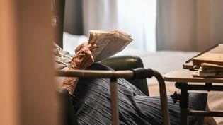 Un résident d'Ehpad lit dans sa chambre, à Paris (STEPHANE DE SAKUTIN / AFP)