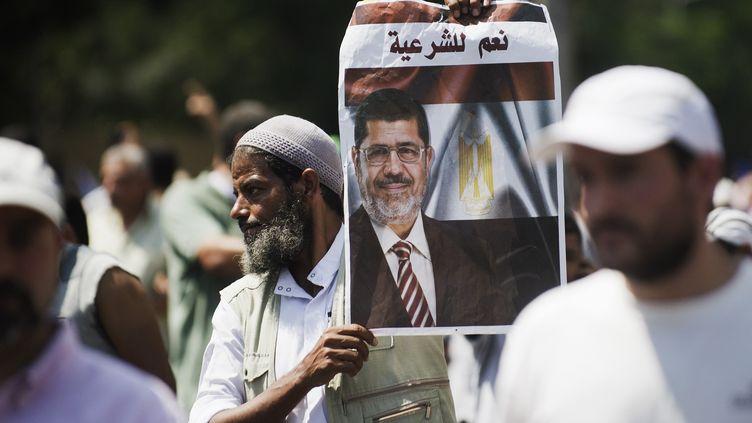 Les manifestants brandissent le portrait de Mohamed Morsi, l'ex-président destitué, auCaire (Egypte), le 5 juillet 2013. (GIANLUIGI GUERCIA / AFP)