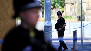 Des policiers britanniques gardent la zone qui entoure la Manchester Arena, le 23 mai 2017, au lendemain d'un attentat dans cette salle de concert. (JON SUPER / AFP)