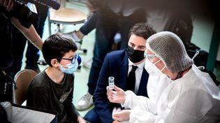 Le porte-parole du gouvernement, Gabriel Attal, assiste au lancement de la campagne de tests salivaires contre le Covid-19 dans une école de Lyon (Rhône), le 26 février 2021. (MARINE GONARD / HANS LUCAS / AFP)