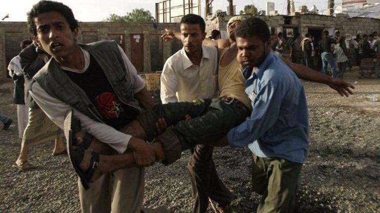 Des manifestants anti-gouvernement évacuent l'un des leurs, blessé dans des heurts, le 11 mai 2011 à Sanaa (AFP / Mohammed Huwais)