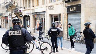 Des policiers contrôlent des passants dans les rues de Bordeaux, le 17 mars 2020,après la mise en place du confinement. (CONSTANT FORME-BECHERAT / HANS LUCAS / AFP)