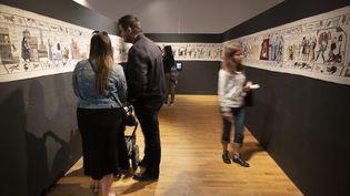 """Des visiteurs contemplent la tapisserie dédiée à la série """"Game of Thrones"""" le 5 juillet 2019 au musée de Belfast. (PAUL FAITH / AFP)"""