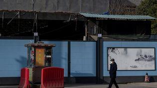 Un homme passe devant le marché de poissons de Wuhan (Chine), le 11 janvier 2021. (NICOLAS ASFOURI / AFP)