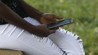 Une Africaine utilise un téléphone portable (photo prise le 3 mars 2017). (AFP - GODONG / BSIP)