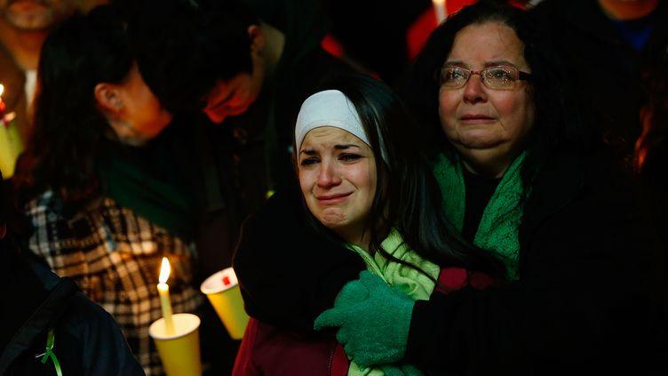 La mère et la sœur de Victoria Soto, institutrice à l'école de Sandy Hook, à Newtown, dans le Connecticut (Etats-Unis) lors d'une veillée en hommage aux victimes de la tuerie, le 15 décembre 2012 à Stratford. (JARED WICKERHAM / GETTY IMAGES / AFP)