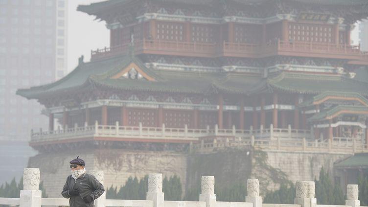 Un homme marche à Nanchang (Chine) sous un épais nuage de pollution, le 5 décembre 2017. (MAXPPP)