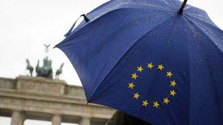 Un passant tient un parapluie aux couleurs du drapeau de l'Union européenne, devant le Bundestag, à Berlin (Allemagne), le 22 mars 2007. (CLEMENS BILAN / AFP)