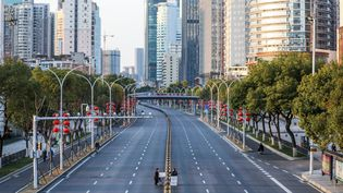 Alors épicentre de l'épidémie de Covid-19, la métropole chinoise de Wuhan est placée sous un confinement strict. Au centre de la photo, deux personnes traversent une route désertée pour livrer des légumes à un hôpital, le 20 février 2020. (AFP)