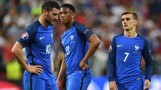 Andre-Pierre Gignac, Anthony Martial etAntoine Griezmann quelques minutes après leur défaite en finale de l'Euro face au Portugal, le 10 juillet 2016. (PATRIK STOLLARZ / AFP)