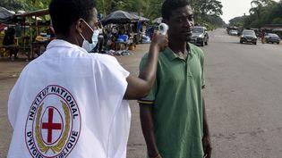 Le 30 mars 2020, un employé de l'Institut national d'hygiène publique contrôle la température d'un homme à Abidjan (Côte d'Ivoire).Les écoles et la plupart des entreprises de la capitale économique ivoirienne ont été fermées. (SIA KAMBOU / AFP)