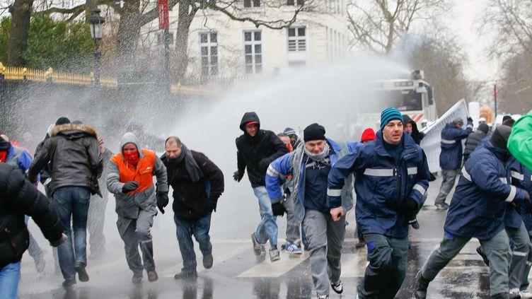 Des salariés belges d'ArcelorMittal repoussés par un canon à eau de la police lors d'une manifestation à Bruxelles (Belgique), le 25 janvier 2013. (BRUNO FAHY / BELGA)