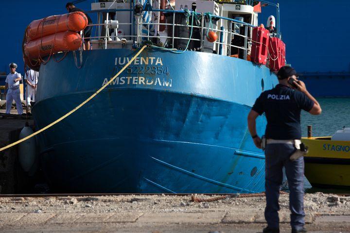 """Un policier italien se tient devant le """"Iuventa"""", navire de l'ONG allemande Jugend Rettet, dans le port de Trapani en Sicile (Italie), le 4 août 2017. (BELLINA FRANCESCO / AFP)"""