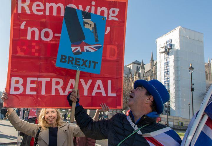 Steve Bray tente de masquer les pancartes des manifestants pro-Brexit, le 26 février 2019, à Londres (Royaume-Uni). (MARIE-VIOLETTE BERNARD / FRANCEINFO)