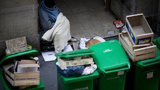 Un sans-abris installé près de poubelles à Paris, le 14 novembre 2012. (JOEL SAGET / AFP)