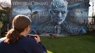 """Une femme prend en photo une fresque représentant le Roi de la nuit dans la série """"Game of Thrones"""" avant la diffusion du dernier épisode, dans un bar de Marina del Rey (Californie, Etats-Unis), le 20 mai 2019. (ROBYN BECK / AFP)"""