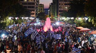 """Des partisans du """"non"""" au référendum célèbrent leur victoire annoncée, dimanche 5 juillet 2015 à Athènes (Grèce). (LOUISA GOULIAMAKI / AFP)"""