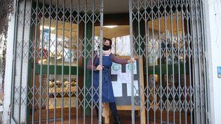 Une commerçante ferme le rideau métallique de son magasin pour respecter l'heure du couvre-feu à 18 heures, àRiedisheim (Haut-Rhin), le 8 janvier 2021. (MAXPPP)