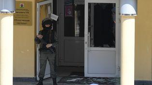 Un policier devant l'école où une fusillade a coûté la vie à 11 personnes, le 11 mai 2021 à Kazan (Russie). (MAKSIM BOGODVID / SPUTNIK)