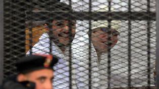 Ahmed Douma (à gauche) et Ahmed Maher (à droite), lors de leur procès au Caire, le 22 décembre 2013. (AFP)