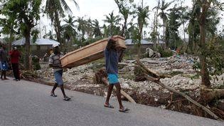 Des habitants portent un cercueil après le passage de l'ouragan Matthew, le 6 octobre 2016, à Cavaillon (Haïti). (ANDRES MARTINEZ CASARES / REUTERS)