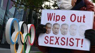 Un manifestant tient un slogan alors qu'il participe à un rassemblement contre le président de Tokyo 2020, Yoshiro Mori, devant le musée olympique à Tokyo, le 11 février 2021. (PHILIP FONG / AFP)