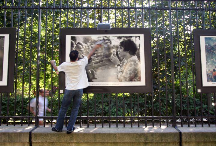 """Une personne nettoire un tirage de """"La jeune fille à la fleur"""", de Marc Riboud, exposée sur la grille du jardin du Luxembourg, le 8 juin 2005. (DAMIEN MEYER / AFP)"""