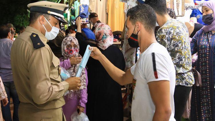 Distribution de masques sanitaires par la police le 17 août 2020 dans les rues de Marrakech, la capitale touristique du Maroc. (STR / AFP)