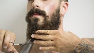 Un homme tatoué se coupe la barbe avec une paire de ciseaux. (HERO IMAGES / GETTY)