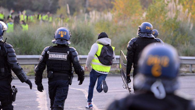 Un gilet jaune et des gendarmes à Bordeaux, le 19 novembre 2018. (NICOLAS TUCAT / AFP)
