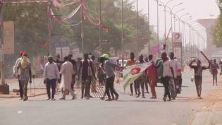 Dans cette image fixe tirée d'une vidéo, des manifestants brandissent des bâtons et tiennent une photo du candidat de l'opposition à la présidentielle, Mahamane Ousmane, le lendemain du rejet des résultatsdu scrutinqui ont donné à son adversaire Mohamed Bazoum, le candidat du pouvoir, une majorité des voix, à Niamey, la capitale nigérienne, le 24 février 2021. (REUTERS/REUTERS TV)