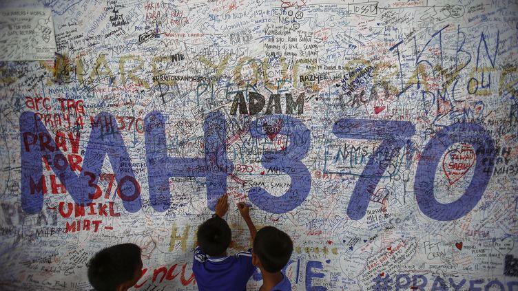 Des enfants dessinent sur un mur d'hommages et de prières aux disparus du vol MH370, le 14 juin 2014 à l'aéroport de Kuala Lumpur (Malaisie). (SAMSUL RAID / REUTERS)