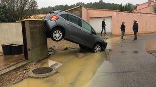 Des habitants deVillegailhenc (Aude) près d'une voiture emportée par les flots, le 15 octobre 2018. (ERIC CABANIS / AFP)
