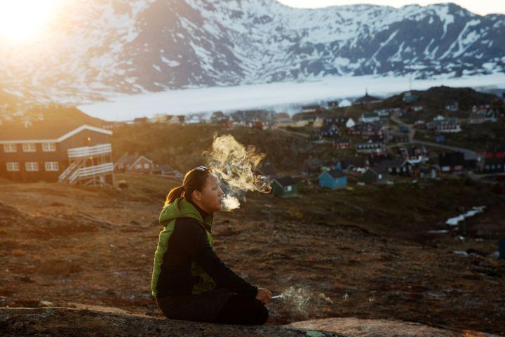 Une jeune femme fume une cigarette aux abords de la ville de Tasiilaq, au Groenland, à l'avant-poste du réchauffement climatique, le 18 juin 2018. (LUCAS JACKSON / REUTERS)