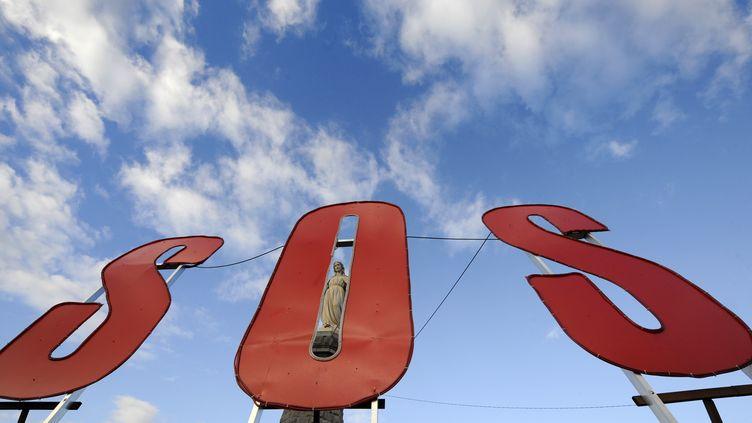 Les lettres SOS devant la statue de la Vierge dressée à flanc de colline et qui domine les hauts fourneaux implantés sur la commune de Hayange (Moselle), le 30 novembre 2012. (JEAN-CHRISTOPHE VERHAEGEN / AFP)