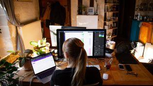Une femme installée dans son salon travaille à distance, à Angers (Maine-et-Loire), le 30 mars 2020. (THIBAUD VAERMAN / HANS LUCAS / AFP)