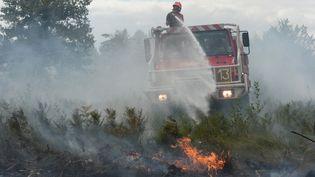 Un sapeur-pompier tente d'éteindre l'incendie qui a touché la commune de Saint-Jean-d'Illac (Gironde), le 25 juillet 2015. (MEHDI FEDOUACH / AFP)