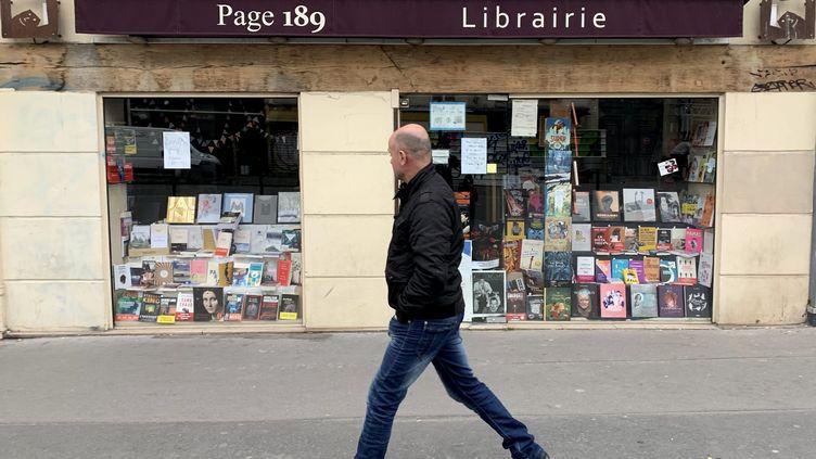Un passantjette un œil sur une librairie fermée, à Paris, rue du Faubourg Saint-Antoine, le 21 mars 2020, quelques jours après l'entrée en vigueur du confinement. (DELPHINE GOLDSZTEJN / MAXPPP)