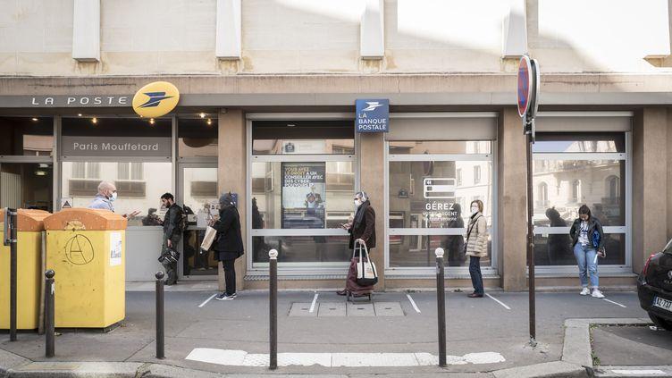 Despersonnes font la queue, le 21 mars 2020, devant un bureau de poste à Paris, en respectant les distances de sécurité.Photo d'illustration. (ADRIEN VAUTIER / LE PICTORIUM / MAXPPP)