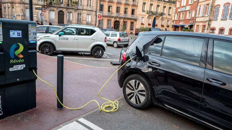 Une voiture est rechargée dans une borne en libre-service pour les véhicules électriques ou hybrides dans le centre ville de Toulouse, le 22 mai 2021. (FREDERIC SCHEIBER / HANS LUCAS  / AFP)