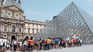 Des visiteurs attendent à l'entrée de la pyramide du Louvre. Juillet 2015.  (MIGUEL MEDINA / AFP)
