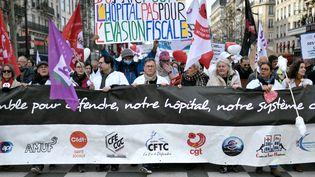 """Des soignants tiennent une banderole """"ensemble pour défendre notre hopital et notre système de santé"""" lors d'une manifestation à Paris, le 14 février 2020. (STEPHANE DE SAKUTIN / AFP)"""