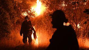 Des pompiers tentent de défendre une maison face à l'incendie Ranch Fire qui sévit près de la ville de Upper Lake en Californie, le 2 août 2018. (MARK RALSTON / AFP)