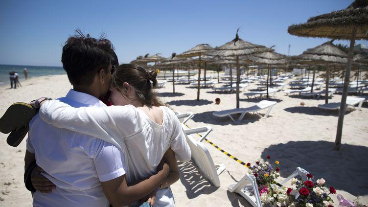 Des touristes viennent se recueillirsur la plage où 38 personnes ont été tuées à Sousse (Tunisie), vendredi 26 juin 2015. (KENZO TRIBOUILLARD / AFP)